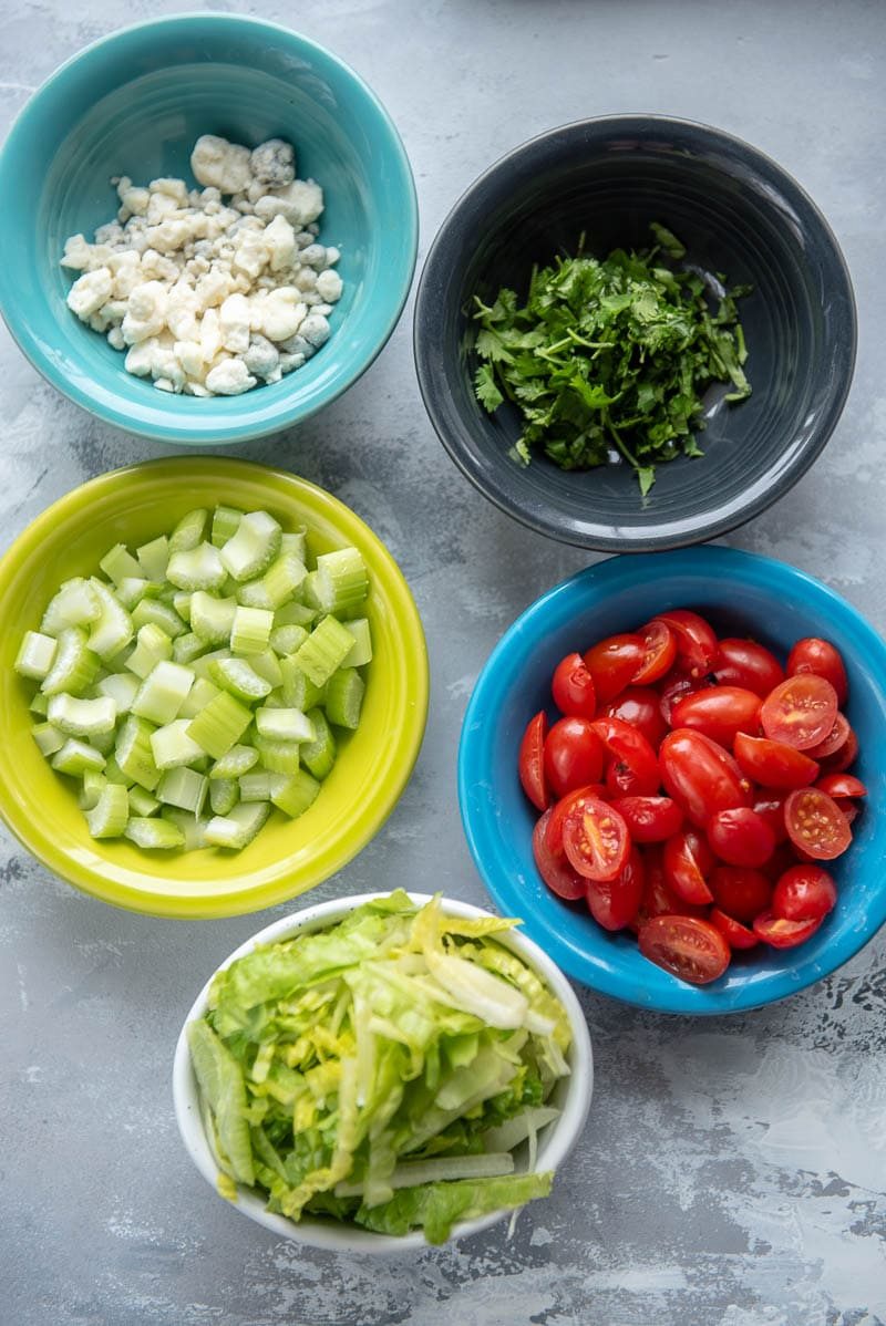onions, bell peppers, tomatoes, and lettuce in bowls