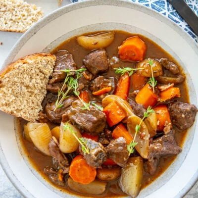 slow cooker beef bourguignon in a white bowl with bread and a spoon