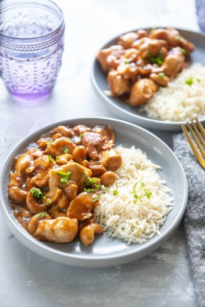 cashew chicken with rice on two plates with a glass of water
