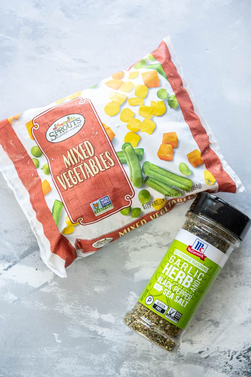 bag of frozen mixed vegetables and bottle of herb and garlic seasoning