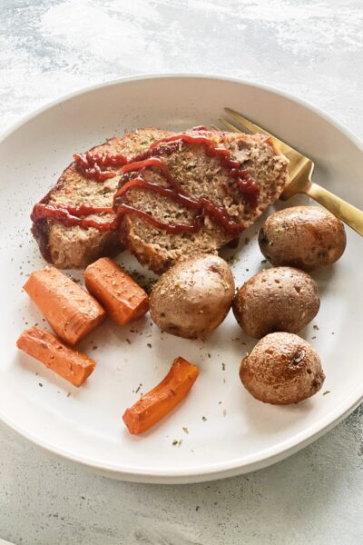 turkey meatloaf on a plate with carrots and potatoes