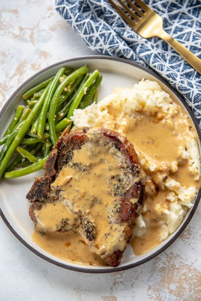 pork chop with mashed potatoes and green beans on a white plate topped with gravy