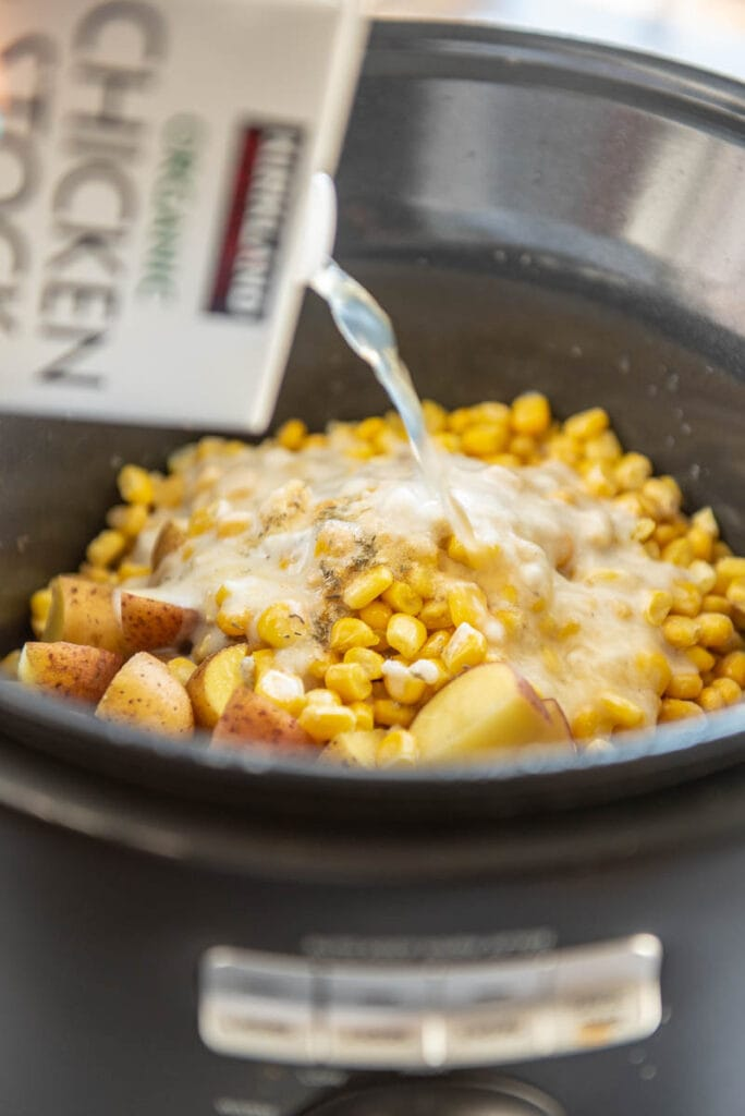pouring broth over corn and potatoes in slow cooker