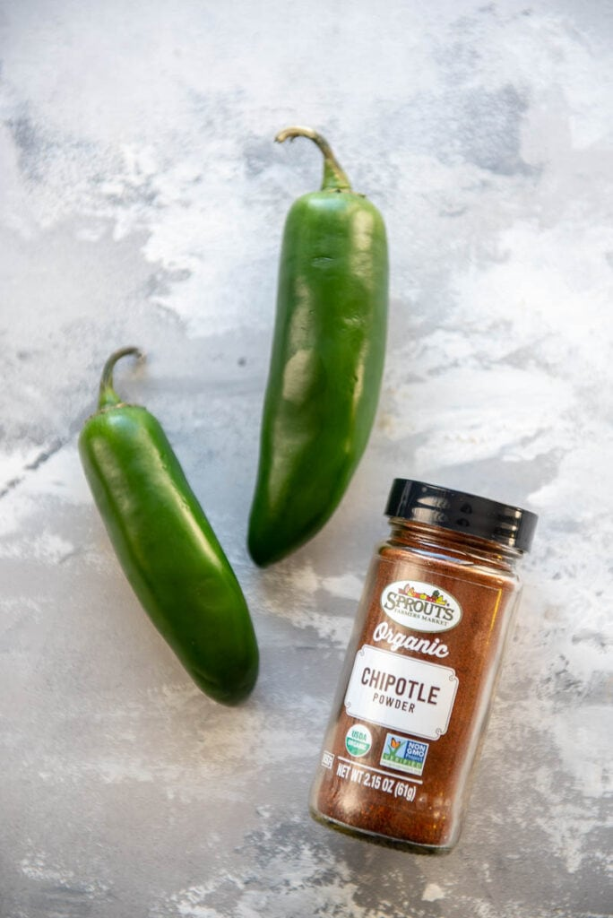 two jalapeño peppers and a jar of chipotle powder
