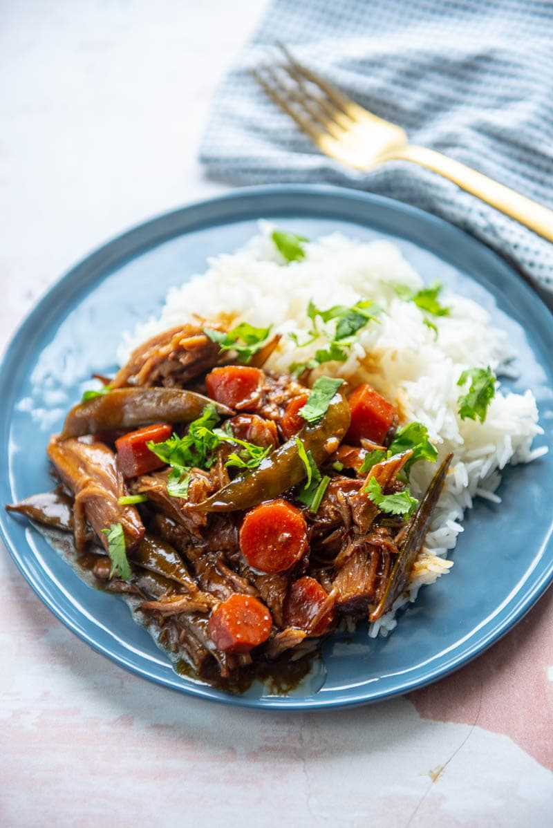 ginger pork on a blue plate with a fork