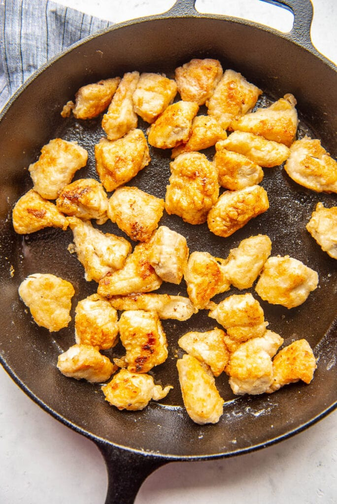 coated chicken pieces in a fry pan
