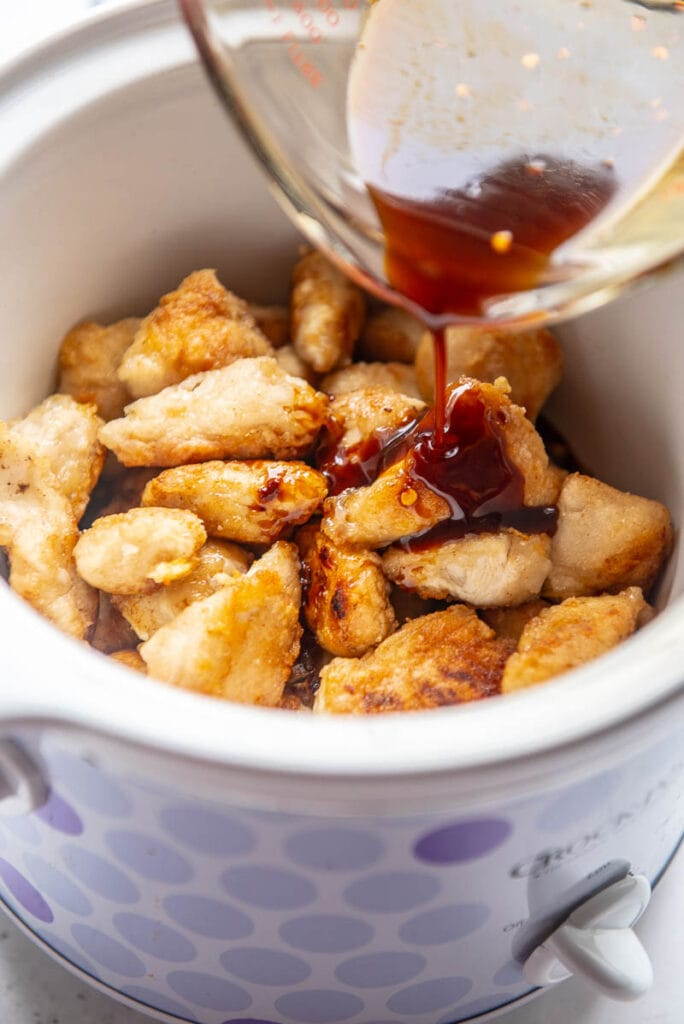 general tso sauce poured on chicken pieces in a slow cooker