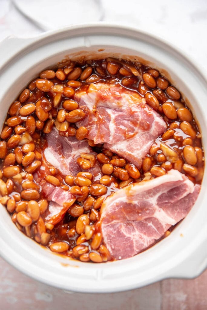 pintos, bbq, sauce, and pork shoulder in a slow cooker