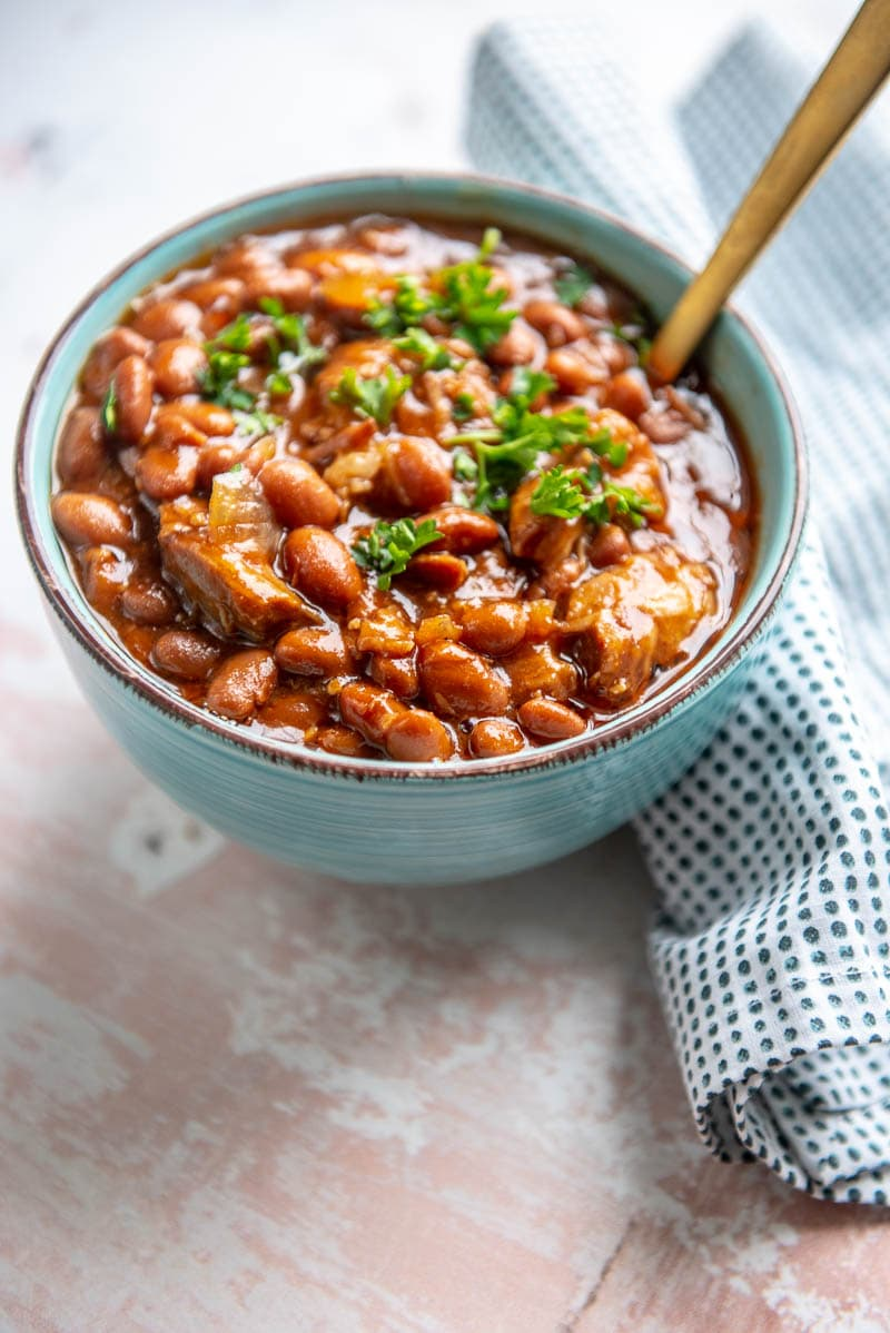 slow cooker pork and beans in a bowl with a spoon
