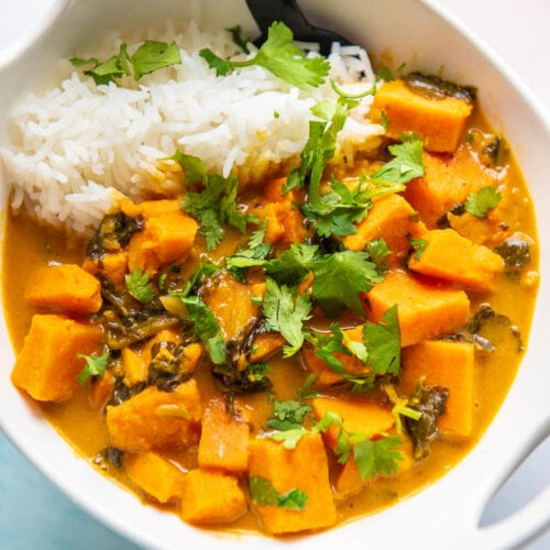 sweet potato curry in a white bowl with spoon