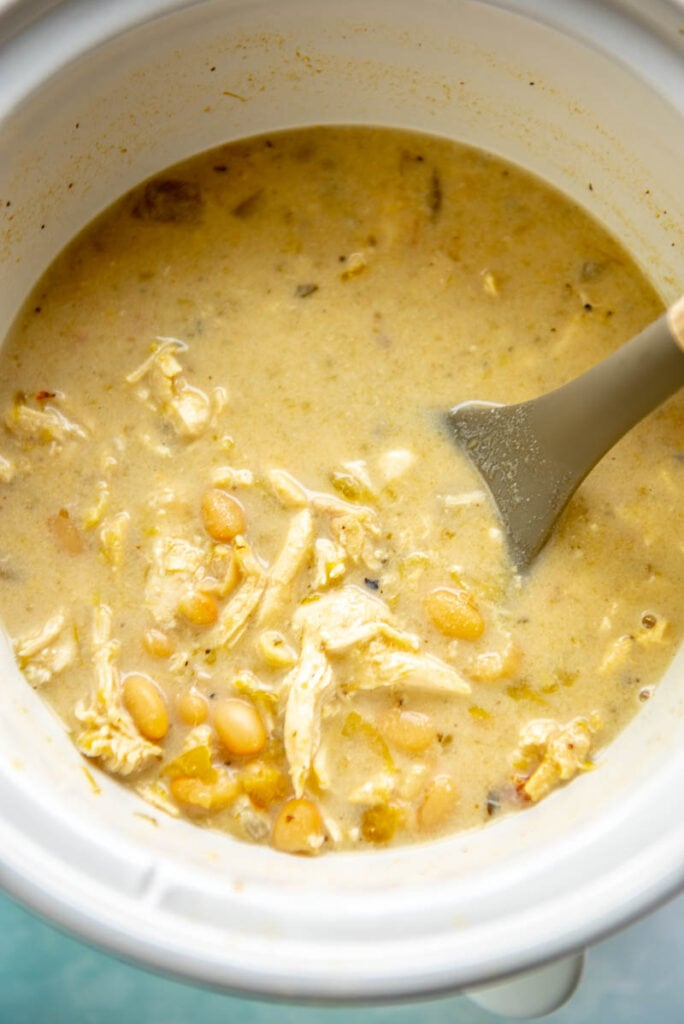 white chicken chili with shredded chicken in slow cooker with spoon
