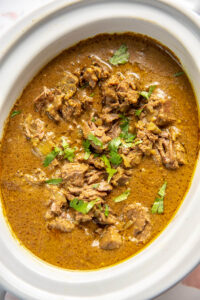 white oval slow cooker filled with flavorful beef curry