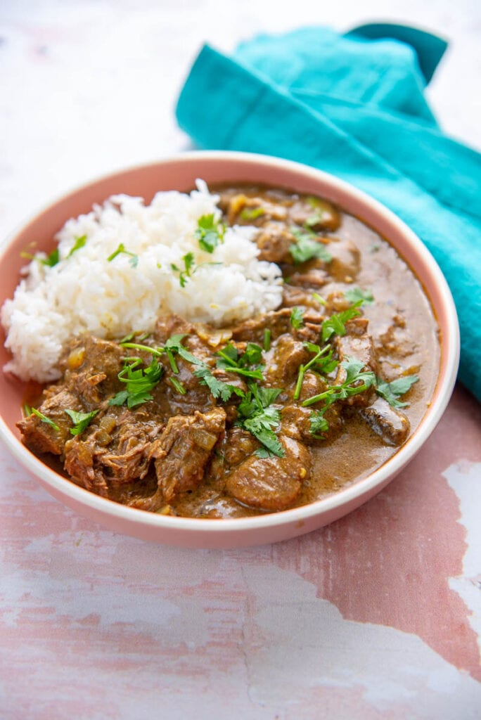 pink bowl filled with rice and beef curry