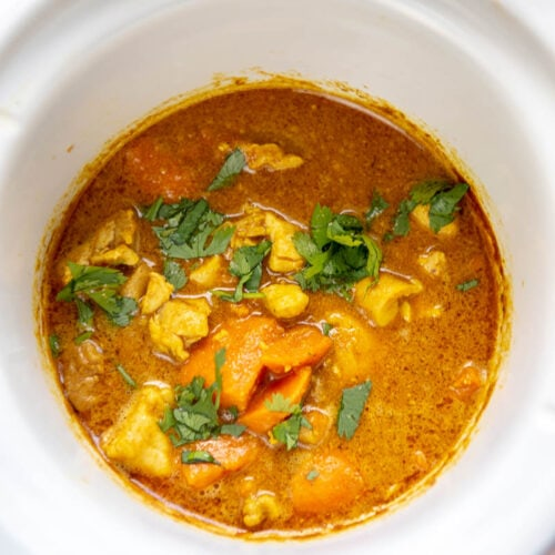 white round slow cooker with chicken korma and sauce