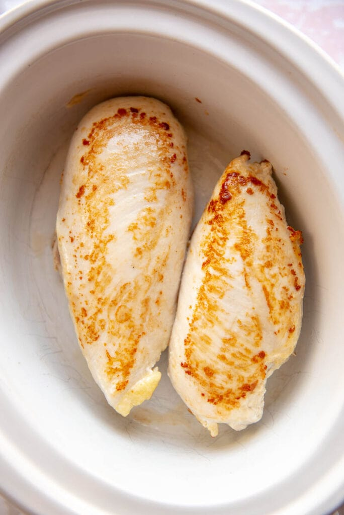 two browned chicken breasts in a slow cooker