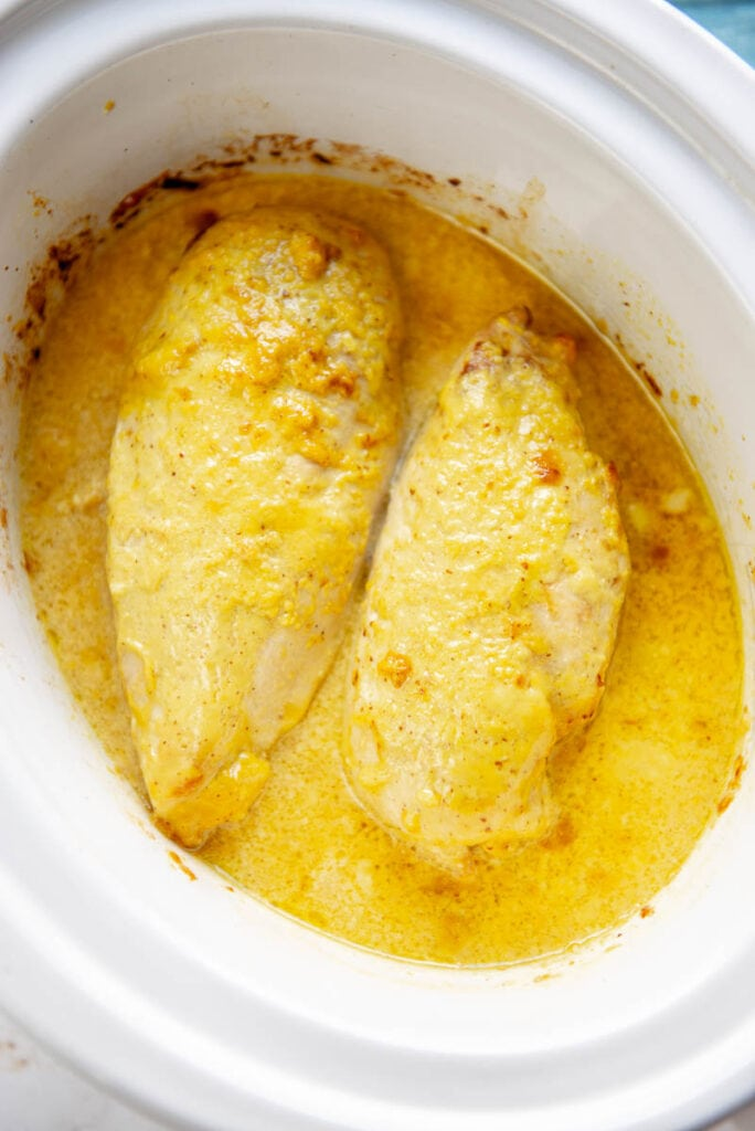 two cooked chicken breasts and honey mustard sauce in a slow cooker