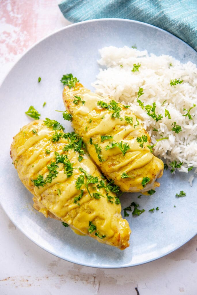 two honey mustard chicken breasts on a plate with mashed potatoes