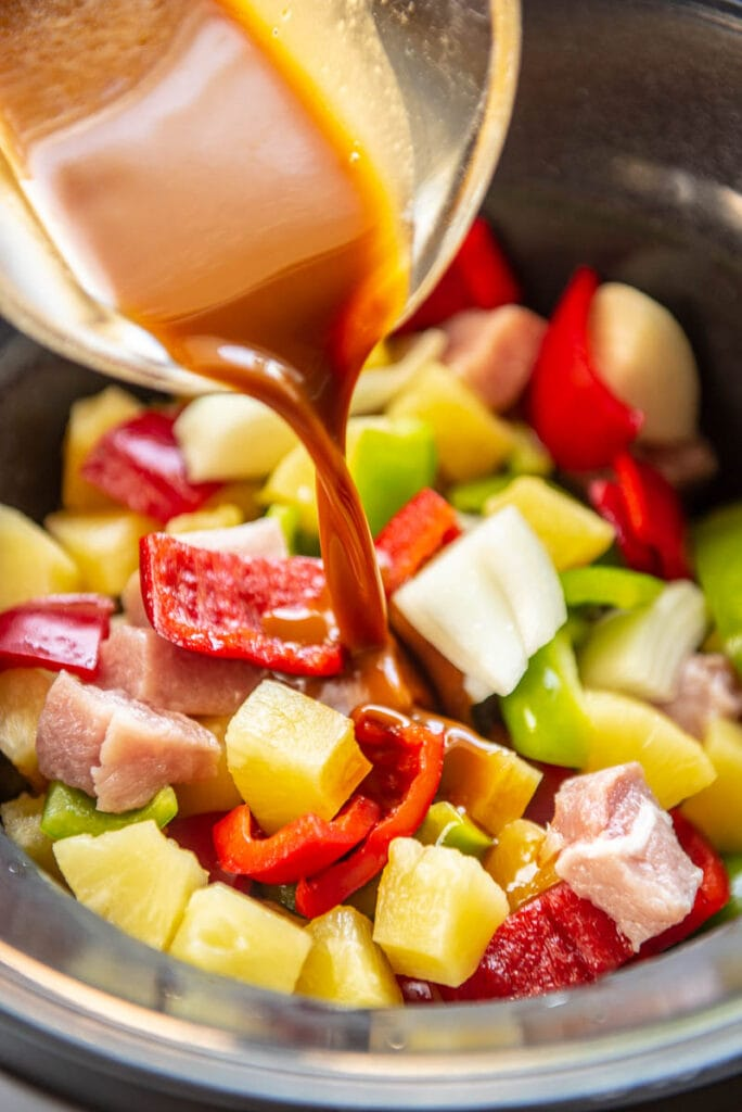 sweet and sour sauce poured over pork and veggies in a slow cooker