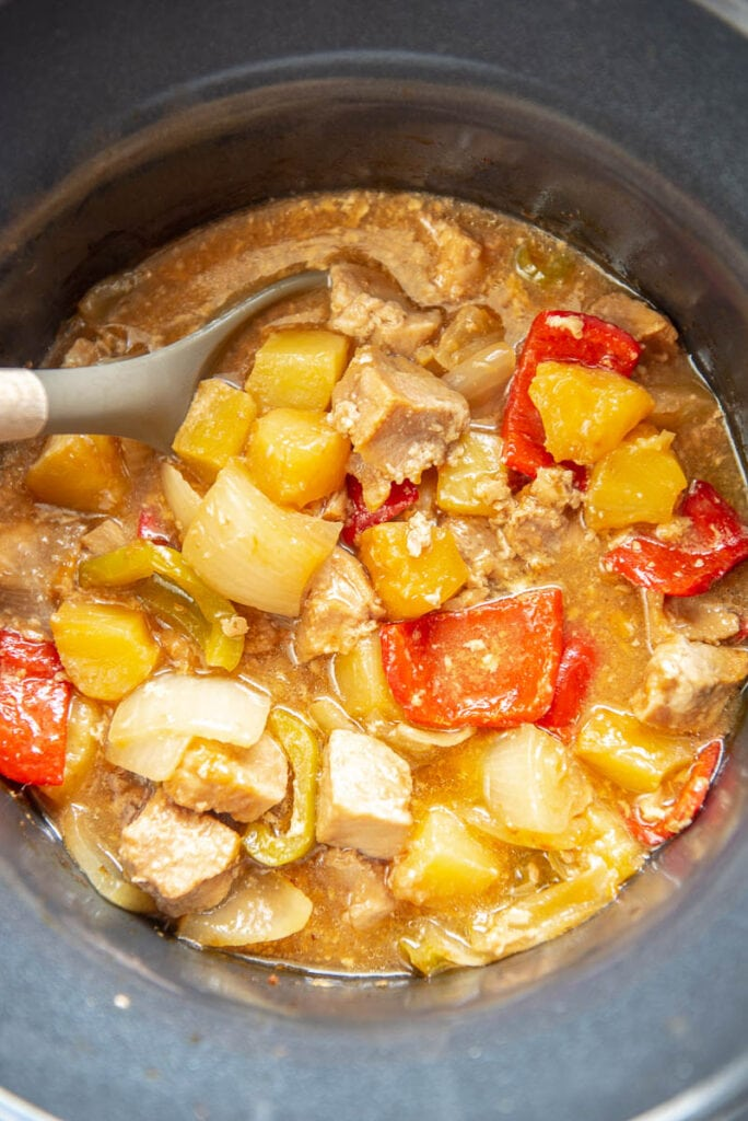 sweet and sour pork in slow cooker with spoon