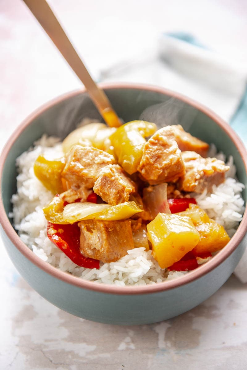 sweet and sour pork over rice in a bowl with spoon