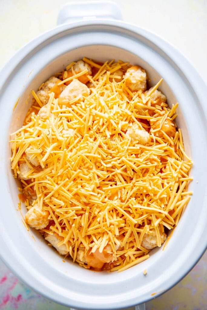 tater tots in white slow cooker topped with cheese