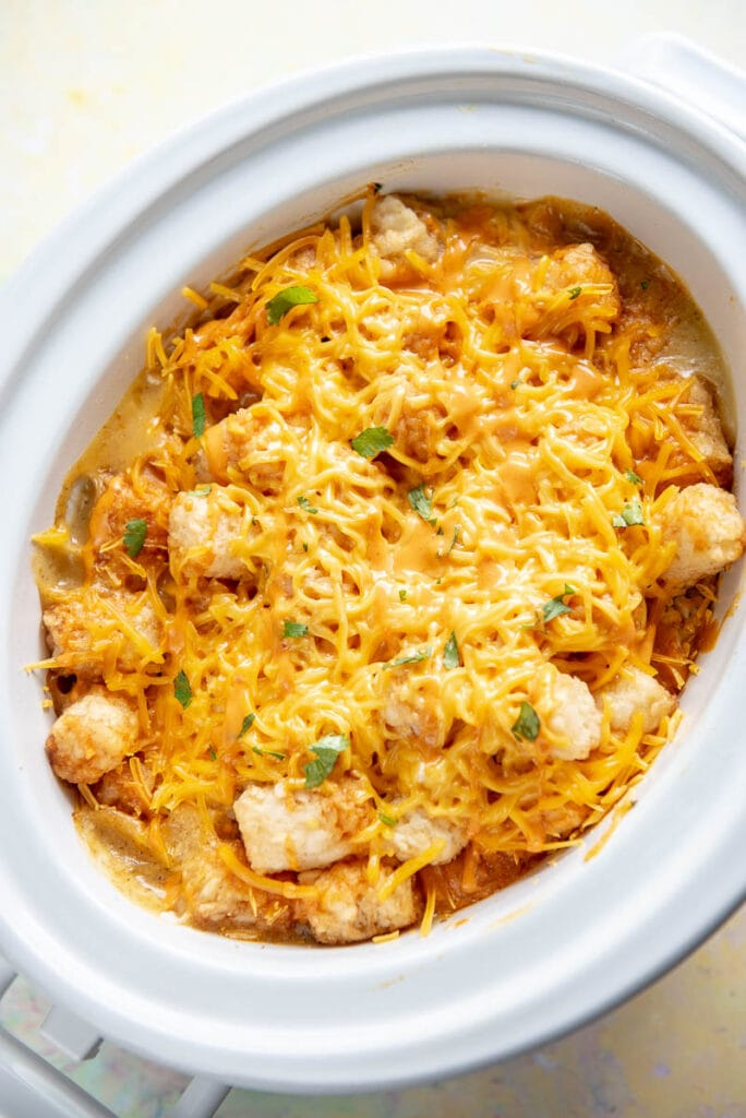 oval casserole slow cooker filled with buffalo chicken tater tot casserole with melted cheese