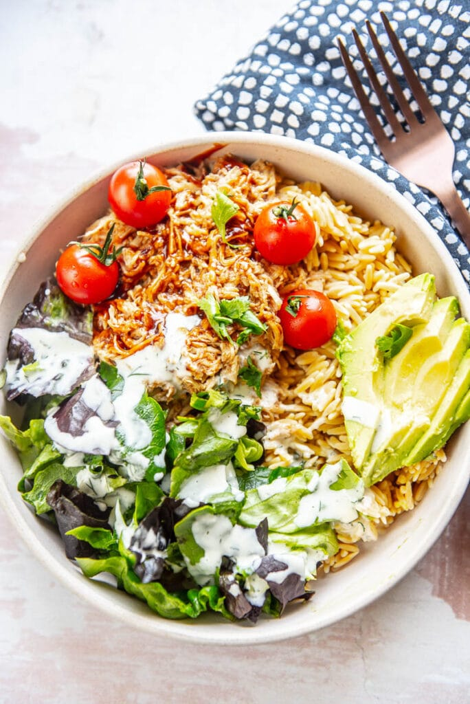 overhead view of bowl filled with lettuce, shredded chicken, avocado and tomatoes