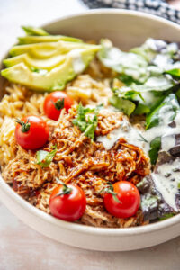 shredded bbq chicken in bowl topped with tomatoes, avocado and ranch