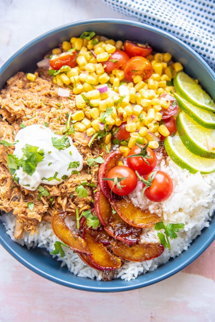 shredded chicken, peaches and corn salsa on a bed of rice in blue bowl