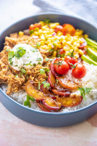 blue bowl filled with chicken, peaches, corn and sour cream