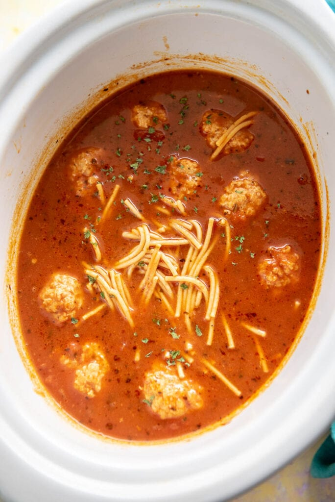 spaghetti and meatball soup in oval white slow cooker
