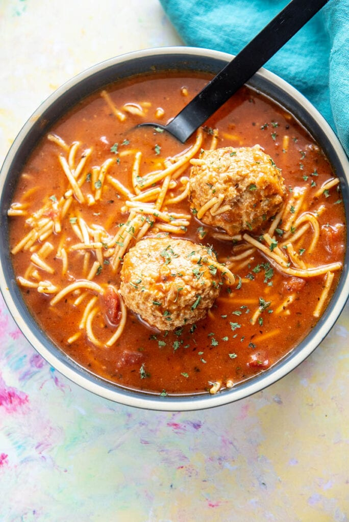 blue bowl filled with spaghetti and meatballs soup