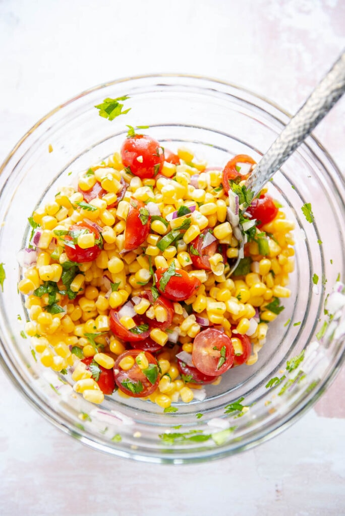 ingredients for tomato corn salsa in a glass bowl with spoon