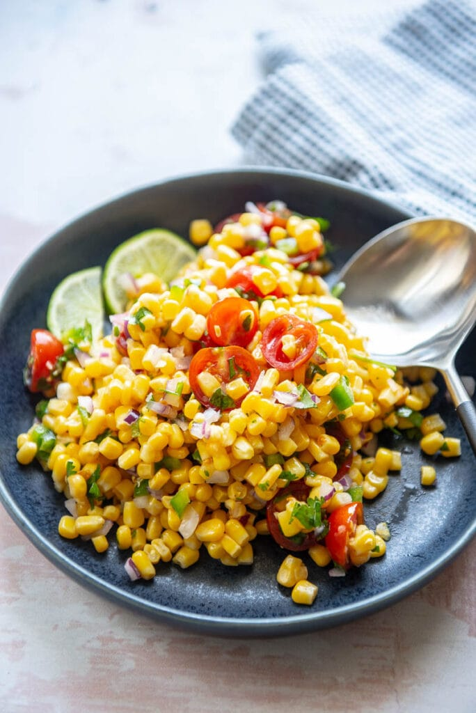 tomato corn salsa on a plate with spoon and lime garnish
