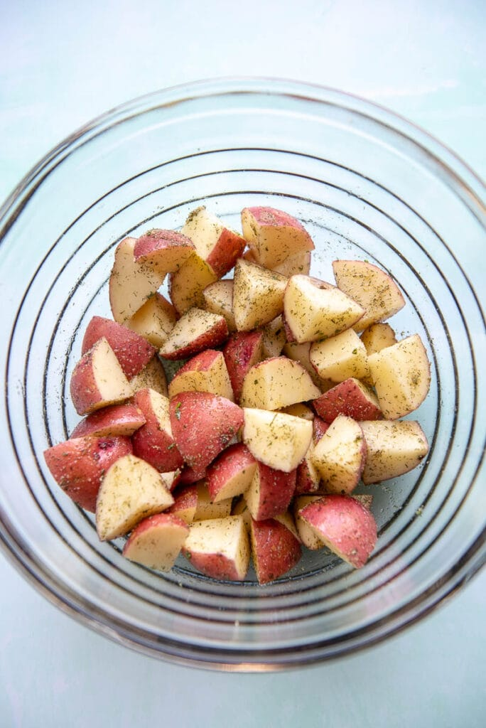glass bowl filled with diced potatoes and sprinkled with seasoning