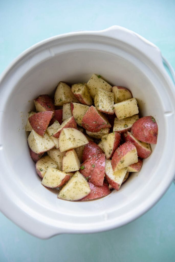 diced and seasoned red potatoes in slow cooker ready to cook