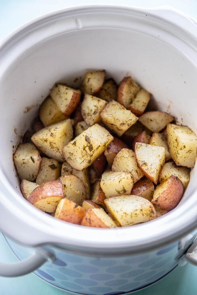 slow cooker filled with cooked red potatoes